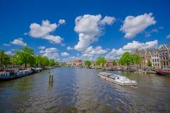 Amsterdam, Paesi Bassi - 10 luglio 2015: Il grande canale idrico che passa la città con parecchie barche ha parcheggiato di fianc Immagine Stock Libera da Diritti