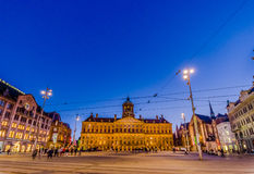 Amsterdam, Paesi Bassi - 10 luglio 2015: Il palazzo reale incredibile come visto attraverso dal quadrato della diga in un bello Fotografie Stock Libere da Diritti