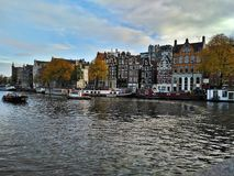 Amsterdam/Paesi Bassi - 30 ottobre 2016: Vista sul canale di Amsterdam, sulle barche e sulle case olandesi tradizionali immagine stock libera da diritti