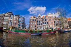 AMSTERDAM, PAYS-BAS, MARS, 10 2018 : Tir extérieur des bateaux-maison et des immeubles sur un canal dans la ville de Photo libre de droits