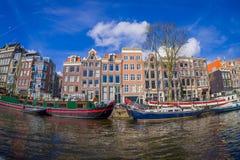 AMSTERDAM, PAYS-BAS, MARS, 10 2018 : Tir extérieur des bateaux-maison et des immeubles sur un canal dans la ville de Photos stock