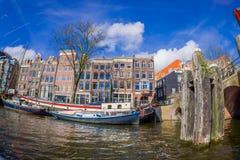 AMSTERDAM, PAYS-BAS, MARS, 10 2018 : Tir extérieur des bateaux-maison et des immeubles sur un canal dans la ville de Photo stock