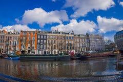 AMSTERDAM, PAYS-BAS, MARS, 10 2018 : Tir extérieur des bateaux-maison et des immeubles sur un canal dans la ville de Photos libres de droits