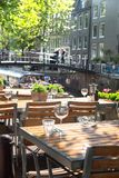 Amsterdam Outdoor Restaurant Dining Tables. Amsterdam restaurant cafe tables set for outdoor dining with glassware and view of canal bridge in the background royalty free stock photos