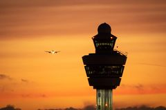 Free Amsterdam Schiphol International Airport Control Tower With A Plane Landing In The Background During Sunset Stock Photo - 166974000