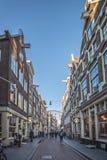 Amsterdam smal gata, i mitten Hela dagen shoppar liv med folk med shoppingpåsar, cyklar, utomhus- butiksinnehavare och Royaltyfria Bilder