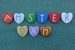 Amsterdam, souvenir with multicolored stone hearts over green sand Royalty Free Stock Images