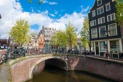 Amsterdam-Stadtbild mit Fahrrädern auf der Brücke während des sonnigen Tages, die Niederlande Stockbilder
