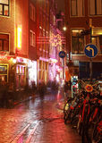 Amsterdam street corner. Amsterdam,Netherlands- October 30th, 2011: Verical image during the night of a wet cobbled street nicely illuminated in Amsterdam Royalty Free Stock Images
