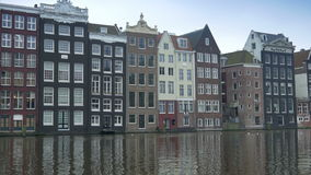 Amsterdam with traditional canal houses 4K. Perspective shot of a canal in Amsterdam with dutch historic houses. The Netherlands stock video