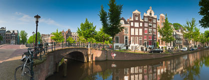 Amsterdam tranquil canal scene, Holland. Pretty dutch doll houses and house boats reflected in the tranquil canals of Amsterdam, Holland Royalty Free Stock Image
