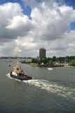 Amsterdam. Tugboat. Port. Towing vessel. High business the building in the distance is visible. In the sky beautiful clouds. Amsterdam. The Netherlands. Europe royalty free stock photography
