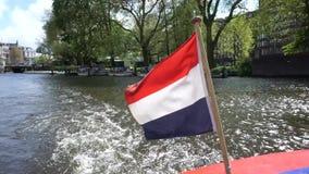 Amsterdam, un bateau avec un drapeau néerlandais banque de vidéos
