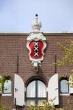 Amsterdam vapensköld på hustopp Arkivfoto