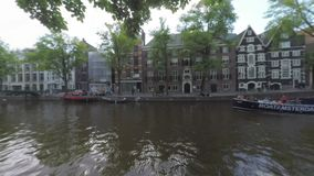 Amsterdam view with boats on the canal, Netherlands. Amsterdam, Netherlands - August 09, 2016: View to the canal and boats sailing along the waterside street stock footage