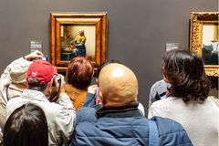 Amsterdam-Visitors looking at the painting milkmaid by Johannes Vermeer stock photography