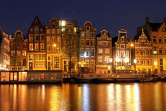 Amsterdam waterfront houses, The Netherlands. Traditional canal houses in Amsterdam, The Netherlands at night. These particular houses are facing the Amstel Stock Photo