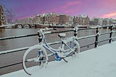 Amsterdam in winter in the Netherlands. Bicycle in Amsterdam the Netherlands covered in snow at sunset Stock Images