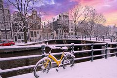 Amsterdam in winter in the Netherlands. Bicycle in Amsterdam the Netherlands covered in snow at sunset Stock Photos