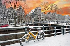 Amsterdam in winter in the Netherlands. Snowy Amsterdam in the Netherlands in winter at sunset Royalty Free Stock Images