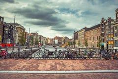 Amsterdam, z kwiatami i bicyklami na mostach nad kanałami, Holandia, holandie Obraz Stock
