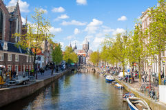 Amsterdam's Red Light District, crowd of tourists go sightseeing, the Church of St. Nicholas is visible in the distance. Stock Images