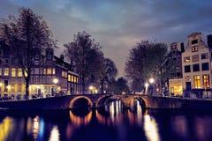 Amterdam运河、桥梁和中世纪房子在晚上 免版税库存图片
