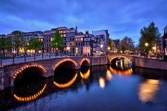 Amterdam运河、桥梁和中世纪房子在晚上 免版税库存照片