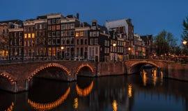 amterdam都市风景早春天夜视图与运河桥梁和中世纪房子的在晚上微明下 库存照片