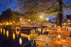 Amterdam cafe tables, canal, bridge and medieval houses in the e Stock Image