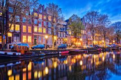 Amterdam canal, boats and medieval houses in the evening. Night view of Amterdam cityscape with canal, boats and medieval houses in the evening twilight Stock Photo