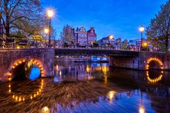 Amterdam canal, bridge and medieval houses in the evening. Night view of Amterdam cityscape with canal, bridge and medieval houses in the evening twilight Royalty Free Stock Photos