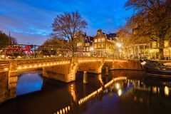 Amterdam canal, bridge and medieval houses in the evening. Night view of Amterdam cityscape with canal, bridge and medieval houses in the evening twilight Stock Photos