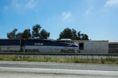 Amtrak train rolling down the rails beside freeway Royalty Free Stock Photo