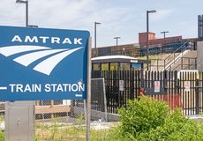 Amtrak train station sign and stairs to trains. Blue Amtrak train station sign and stairs to trains during construction and security black iron fence, downtown stock image