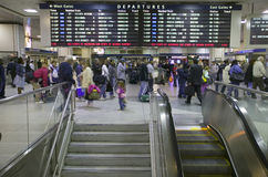 Amtrak train travelers stand in line under Departures sign, while a man goes down escalator at Penn Station, New York City, Manhat Stock Photo