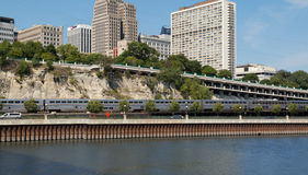 Amtrak train travels along river at St. Paul, Minnesota. An Amtrak passenger train travels along the tracks beside the Mississippi River in downtown Saint Paul Stock Image
