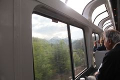 Amtrak viewing car passing mountians. Inside Amtrak viewing car passing though Glacier National Park in Montana. Amtrak has a variety of scenic routes across stock image