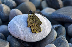 Amulet hand of Fortune. Is on the rocks stock photos