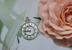 Amuleto d'argento sotto forma di fronte di orologio su un fondo bianco fotografia stock libera da diritti