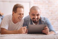 Amusé deux hommes observant des vidéos ensemble Image stock