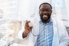Amused African American doctor using medical headphones. Caring about health. Close up amused African American doctor using earphones while pointing at you and royalty free stock photos