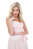 Amused blonde model in pink dress posing a finger on the mouth Stock Image