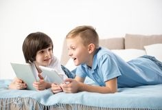 Amused boys relaxing with comfort indoors. Modern children spending their holidays playing new games on tablets. Their faces expressing enjoyment royalty free stock photography