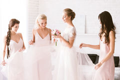 Amused bridesmaids touching the dress of the bride. Look at you. Excited smiling young bridesmaids standing in the white bedroom while helping the bride to get royalty free stock image