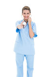 Amused brown haired nurse in blue scrubs playing with her stethoscope Stock Photo