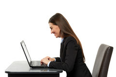 Amused businesswoman with laptop. Amused businesswoman reading on her laptop`s screen on white background Royalty Free Stock Photo