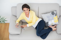 Amused casual brunette in yellow cardigan using a tablet pc Royalty Free Stock Photography