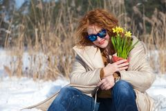 Amused charming woman with blue sunglasses resting in snow while looking down. Optimistic adorable woman looking down through blue sunglasses while holding stock photo