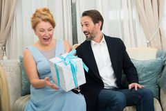 Amused charming woman expressing happiness while receiving a present from her beloved husband. Highly excited. Pleased admirable women in elegant blue dress royalty free stock images